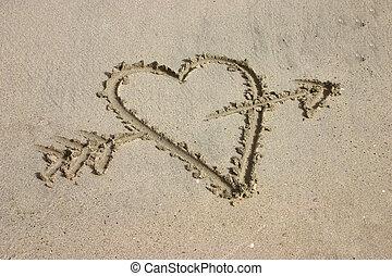 Heart with arrow written in sand