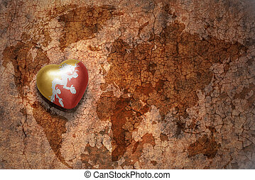 heart with national flag of bhutan on a vintage world map crack paper background.