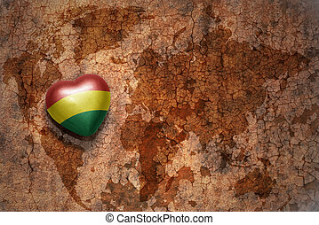 heart with national flag of bolivia on a vintage world map crack paper background. concept