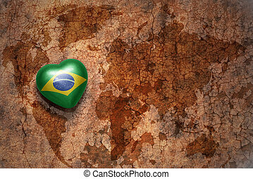 heart with national flag of brazil on a vintage world map crack paper background. concept