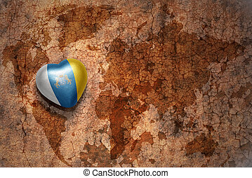 heart with national flag of canary islands on a vintage world map crack paper background. concept