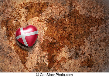heart with national flag of denmark on a vintage world map crack paper background