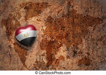 heart with national flag of egypt on a vintage world map crack paper background.