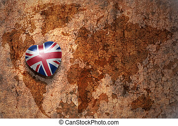 heart with national flag of great britain on a vintage world map crack paper background