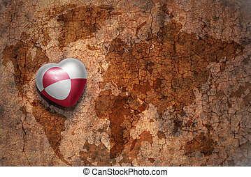 heart with national flag of greenland on a vintage world map crack paper background. concept