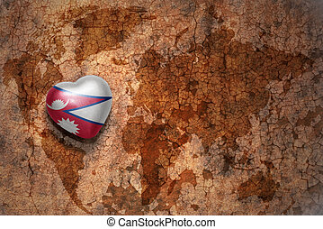 heart with national flag of nepal on a vintage world map crack paper background.
