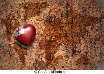 heart with national flag of Tonga on a vintage world map crack paper background. concept