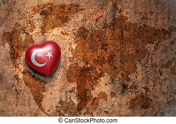 heart with national flag of turkey on a vintage world map crack paper background