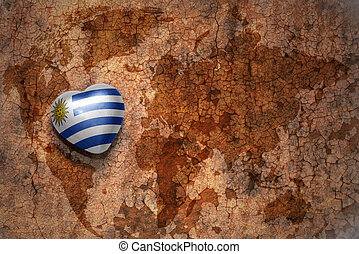 heart with national flag of uruguay on a vintage world map crack paper background. concept