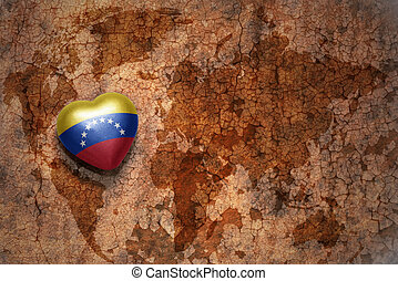heart with national flag of venezuela on a vintage world map crack paper background. concept