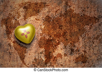 heart with new mexico state flag on a vintage world map crack paper background
