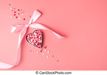 Heart with pink bow on pink background.