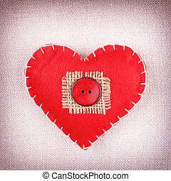 Heart with red button on  vintage fabric background