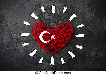 Heart with sun rays and flag of Turkey on a dark background. Theme of rest and travel