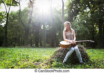Heartbroken woman in nature with guitar