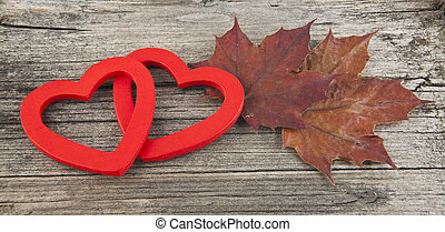 hearts and autumn leaves on wooden background closeup