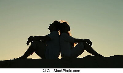 Hearts beating in unison - Silhouettes of lovers sitting...