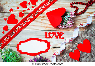 Hearts, flowers, ribbons on a wooden light background