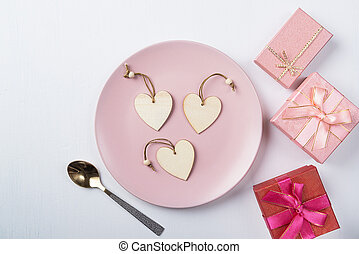 Hearts on a plate and gifts on a white table.