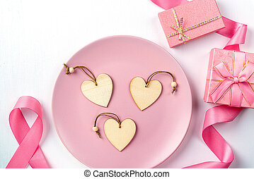 Hearts on a plate, pink ribbon and gifts on a white table.