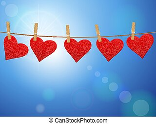 Hearts hanging on clothesline at sky.
