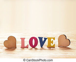 Hearts on wooden background with letters love