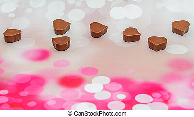 Hearts shape chocolate, Valentines Day sweets, pink bokeh background.