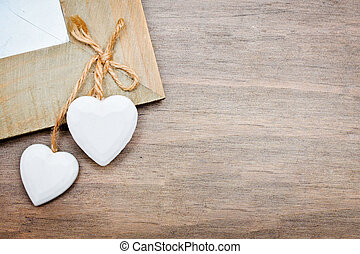 Hearts - Two white hearts on a wooden surface
