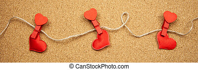 Hearts with clothespins on corkboard background, concept of uncertainty in love