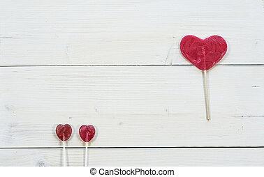 Heartshape red lollipops on white background