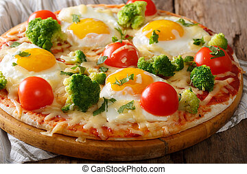 hearty breakfast of pizza with eggs, broccoli, tomatoes closeup on the table. horizontal