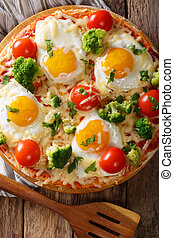 hearty breakfast of pizza with eggs, broccoli, tomatoes closeup on the table. Vertical top view