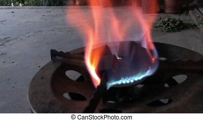 Heating coconut coals on a gas burner close-up In slow motion