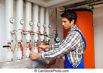 Heating engineer in a boiler room for heating system - Young...