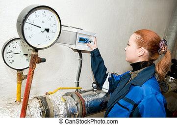 heating engineer in boiler room - woman engineer checking...