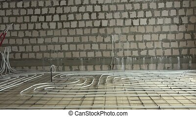 Heating pipes on construction area floor. Energy efficient system. Rooms without walls. Panorama shot