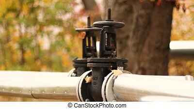 Heating supply concept. Metallic large pipeline with black tap and a valve on the street in the fall season. Industrial structure