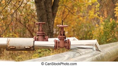 Heating supply concept. Metallic large pipeline with a tap and a valve on the street in the fall season. Building heating system control equipment