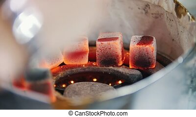 Heating up embers for a hookah. Close up