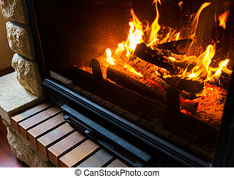 close up of burning fireplace at home - heating, warmth, ...