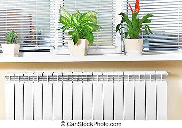 Heating white radiator radiator with flower and window. -...