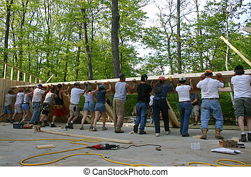 workers raise wall of large new home