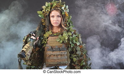 Heavily armed female soldier in battle helmet holding...