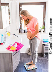 Heavily pregnant woman on scale in bathroom