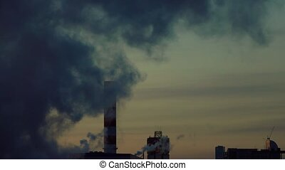 Heavily smoking factory against late evening sky. 4K video