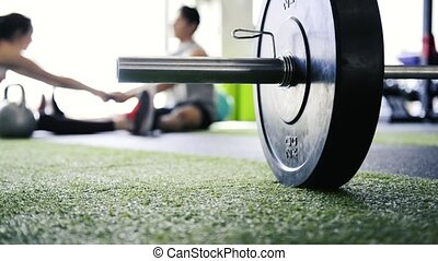 Heavy barbell on the floor in gym. Couple stretching legs. -...