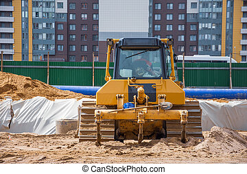 Heavy bulldozer back view on the construction of sewage and heating communications under the road, amid multi-story residential buildings.