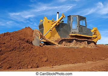 heavy bulldozer moving red sand in sandpit over blue sky