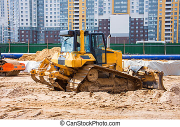 Heavy bulldozer on the construction of sewage and heating communications under the road, amid multi-story residential buildings.