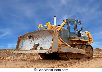 Heavy bulldozer with half raised blade standing in sandpit over bright blue sky. See my other construction machines in portfolio.